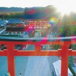 Photo= The Romon gate towers above the vermilion-lacquered torii gate. The emerging morning sun divinely illuminates the gate (October 8, Fushimi Inari Taisha Shrine, Fushimi Ward, Kyoto) = shot from a drone