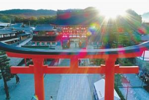Photo= The Romon gate towers above the vermilion-lacquered torii gate. The emerging morning sun divinely illuminates the gate (October 8, Fushimi Inari Taisha Shrine, Fushimi Ward, Kyoto) = shot from a drone