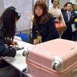 Photo= A tourist checks her suitcase before going out for sightseeing (Kyoto Central Post Office, Shimogyo Ward, Kyoto)