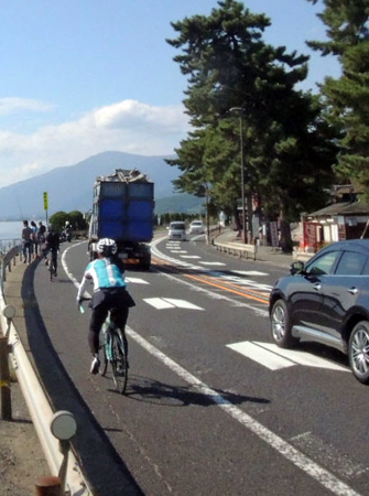 Photo= People enjoying cycling along the Lake Biwa coast. Coexistence between cars and bicycles has become an issue (Ukawa, Takashima City, Shiga Prefecture)