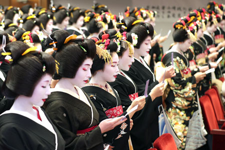 Photo= Geiko and maiko wearing rice-ear-shaped headpins for New Year, recite a chant for their proper attitude, including their devotion to enhancing their art skills (January 7, Gion Corner, Higashiyama Ward, Kyoto)