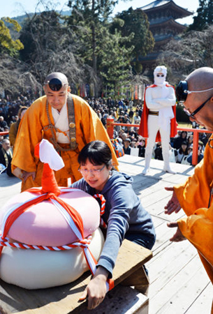 Photo= A challenger in the women's section attempts to lift huge, 90kg Kagami-mochi rice cakes (February 23, Daigoji Temple, Fushimi Ward, Kyoto)