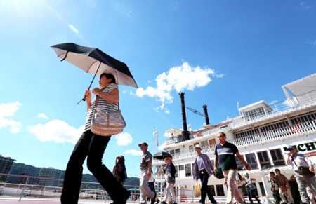 Photo= People disembark from an excursion ship on Lake Biwa with parasols and towels at hand under the harsh sunlight (2:50 p.m., July 23, Otsu Port, Hama Otsu, Otsu City, Shiga Prefecture)