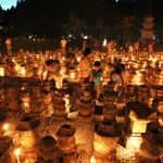 Photo= Worshippers light candles in front of stone towers in the precincts at dusk (August 22, Injo-ji Temple, Kamiyama-cho, Higashiomi City, Shiga Prefecture)