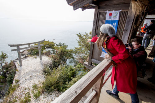 "Photo= A participant throws the ""Kawarake"" tile, aiming at the Torii gate below (November 26, 2017, Tsukubusuma Shrine, Hayazaki-cho, Nagahama City, Shiga Prefecture) = Provided by Nagahama City"