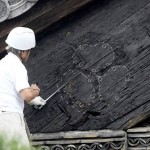 "Photo= The trace of the ""Hollyhock crest"" decoration that was revealed after an ornamental metal fitting was detached by a typhoon. A staff member is checking the trace by marking it with chalk (afternoon, September 23, Nijo Castle, Nakagyo Ward, Kyoto)"
