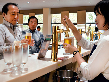 Visitors moisten their throats as they sample beer (Suntory Kyoto Brewery, Nagaokakyo City, Kyoto)