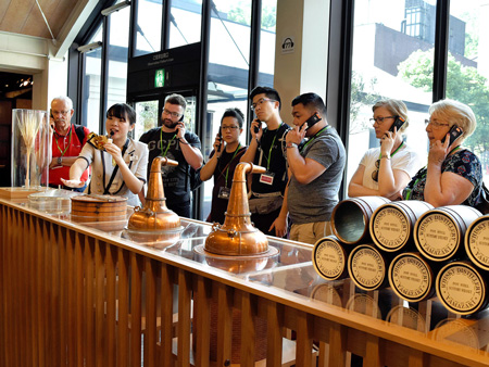 Participants receive an explanation of the whisky manufacturing process. Foreign tourists holding audio guide units stand out (Suntory Yamazaki Distillery, Shimamoto Town, Osaka Prefecture)
