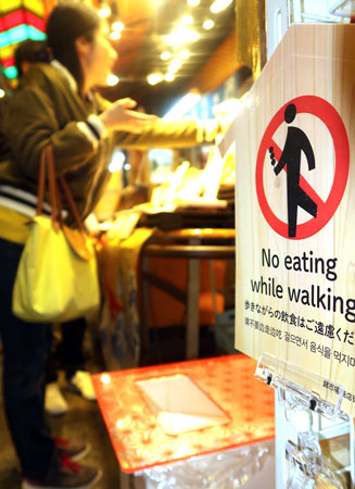 A sign and trash can installed to deter eating in the street (Nishiki Market, Nakagyo Ward, Kyoto)