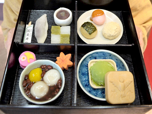 "Photo= ""Shokado Afternoon Tea"" in a quartered box filled with various sweets, including ""Yawata-maki"" made with sweet bean paste (Upper right of upper left quarter) = Yawata Hashiriimochi Roho, Yawata City, Kyoto Prefecture"
