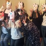 Students strike a pose after finishing free painting on paper fox masks