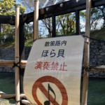 "The ""DO NOT BLOW CONCH SHELL HORNS"" sign installed on the promenade north of Nijo-jo Castle (Nakagyo Ward, Kyoto)"