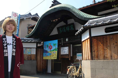 "The public bathhouse ""Yoki-yu"" with its characteristic magnificent undulating gable and its landlady Yukina Fujiuchi. She said, ""I would like the neighbors to recognize its appeal again."" (Sakaemachi, Otsu City, Shiga Prefecture)"