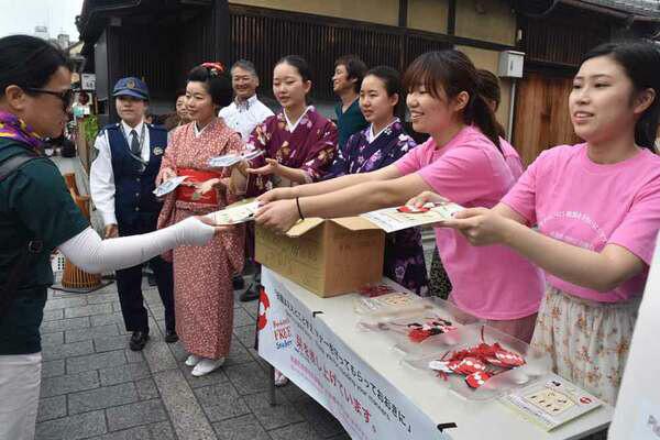 Students and Maiko distributing stickers to tourists on Hanamikoji-dori Street (May 2019, Higashiyama Ward, Kyoto)