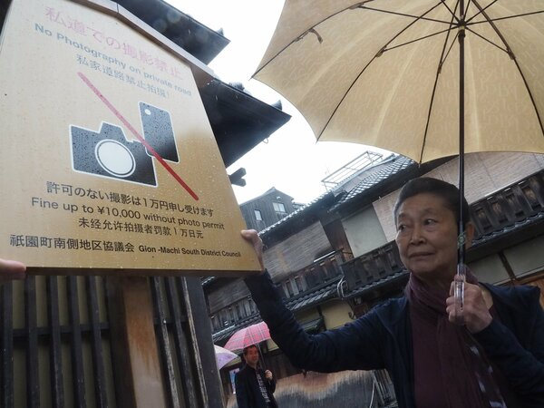 "A notice board announces the photography prohibition on private roads to tourists. Additional sentences explain the stricter measures by stating, ""Fine up to 10,000 yen without photo permit"" (Hanamikoji-dori Shijo-sagaru, Higashiyama Ward, Kyoto)"