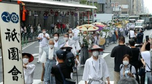 "Representatives of earlier festival floats' preservation groups hold ""sakaki"" wands as they walk eastward along Shijo-dori Street (9:00 a.m., July 17, Shijo-dori Higashinotoin intersection, Shimogyo Ward, Kyoto)"